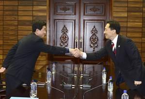 Chefe da delegação norte-coreana, Parque Yong-il (à esquerda) aperta a mão de seu colega sul-coreano Lee Duk-haeng durante as negociações em Panmunjom, zona desmilitarizada que separa as duas Coreias Foto: YONHAP / REUTERS