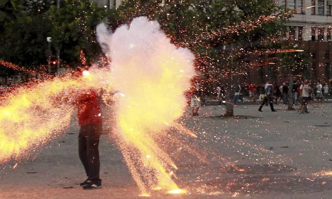 Cinegrafista é cercado pelo fogo do explosivo: artefato foi atirado durante protesto no Centro Foto: Agência O Globo