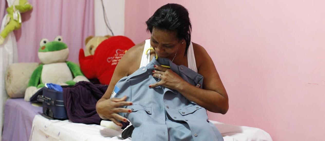 """Maria Rosalina acaricia a farda da Polícia Militar usada pela filha assassinada no Alemão: """"Parece que eles (bandidos) têm mais valor"""" Foto: Pablo Jacob / O Globo"""