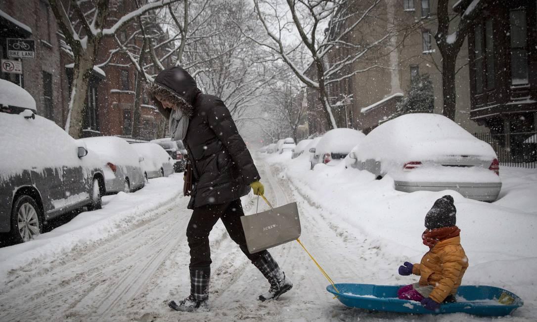 Uma mulher puxa a criança em um trenó, no Brooklyn, em Nova York BRENDAN MCDERMID / REUTERS