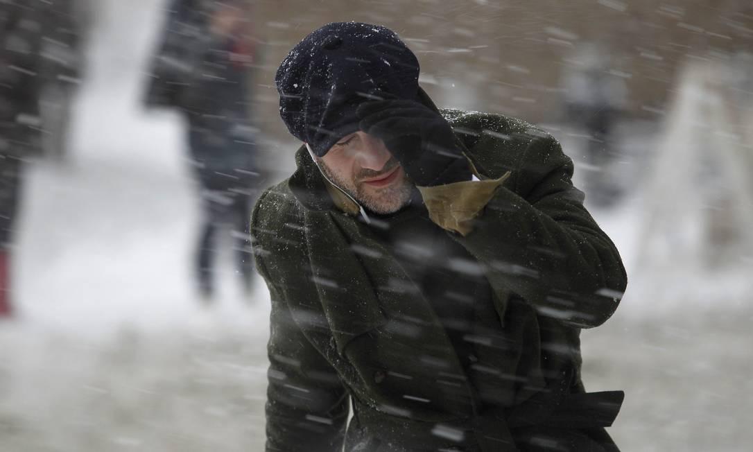 Um homem caminha durante a nevasca na Broadway, em Nova York JOSHUA LOTT / REUTERS