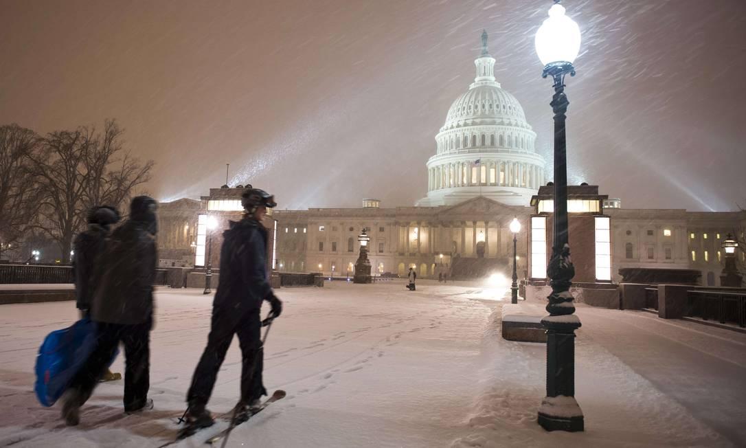 Homem usa skis para se deslocar em frente à sede do Congresso, em Washington MLADEN ANTONOV / AFP