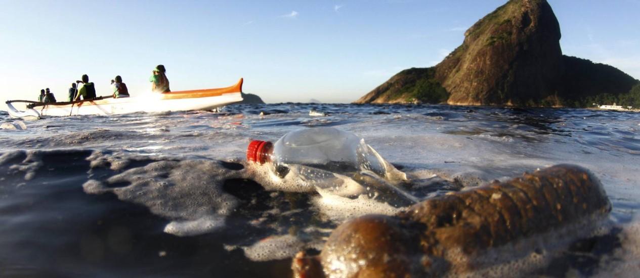 De frente para o Pão de Açúcar, grupo de remadores numa canoa havaiana corta uma extensa ilha de lixo e espuma: pequenas embarcações usadas no esporte já encalharam em meio a detritos na Baía de Guanabara Foto: Marcelo Piu / Agência O Globo