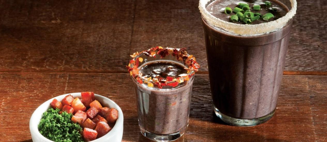 No Devassa, o caldo de feijão, além de ser acompanhado de salsa e bacon, vem em dois copos: um com pimenta e outro com farofinha na borda Foto: Divulgação/Alexander Landau / Agência O Globo