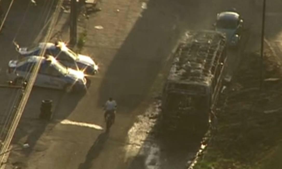 Carros da PM ficam ao lado de ônibus incendiado na Vila Kennedy Foto: Reprodução TV Globo