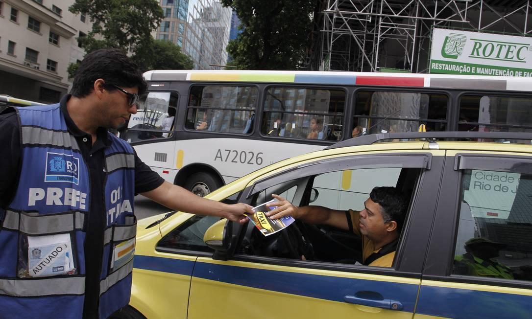 Operador de trânsito distribui panfleto para taxistas no acesso à Avenida Rio Branco Márcia Foletto / Agência O Globo