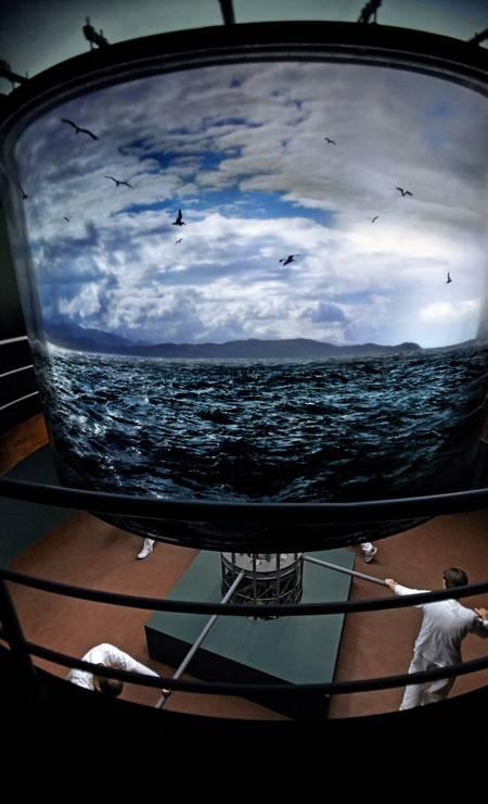 """""""Abajur"""" (1997/2010), de Cildo Meireles. Pessoas acionam uma estrutura cilíndrica que gira e mostra imagens do mar Foto: Divulgação"""