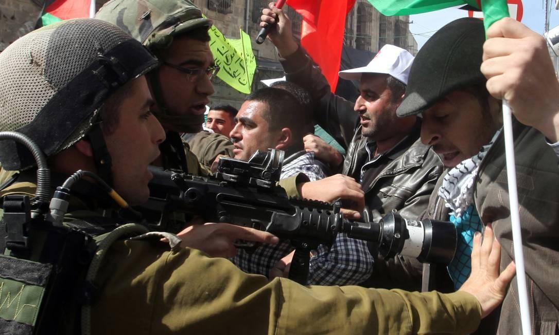 Soldado israelense aponta arma para manifestante na Cisjordânia no 29º aniversário de massacra de 29 muçulmanos palestinos por extremistas judeus Foto: HAZEM BADER / AFP