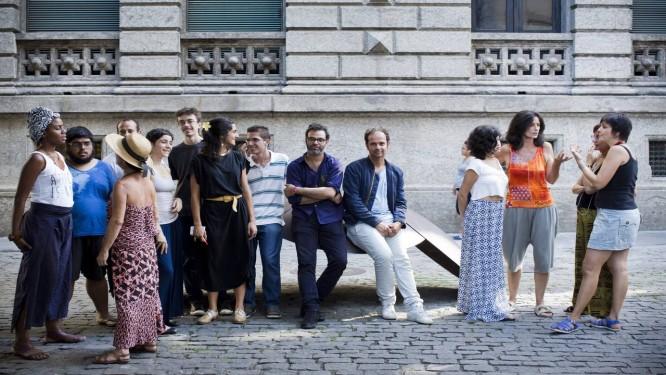 O artista (de calça clara e casaco azul) ao lado de o produtor e diretor da mostra, Asad Raza (de braços cruzados), entre os participantes da obra 'Essas associações' Foto: Mônica Imbuzeiro / Mônica Imbuzeiro