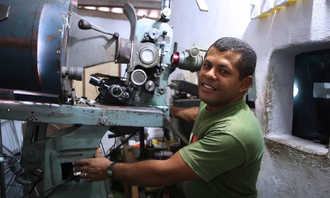 Regilson e seu projetor, montado com peças de dois equipamentos antigos Foto: Agência O Globo