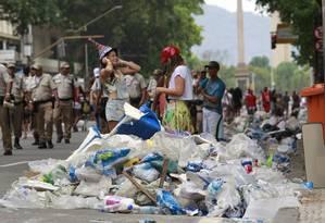 Foliãs caminham em meio ao lixo que toma a Av. Rio Branco Foto: Domingos Peixoto / O Globo