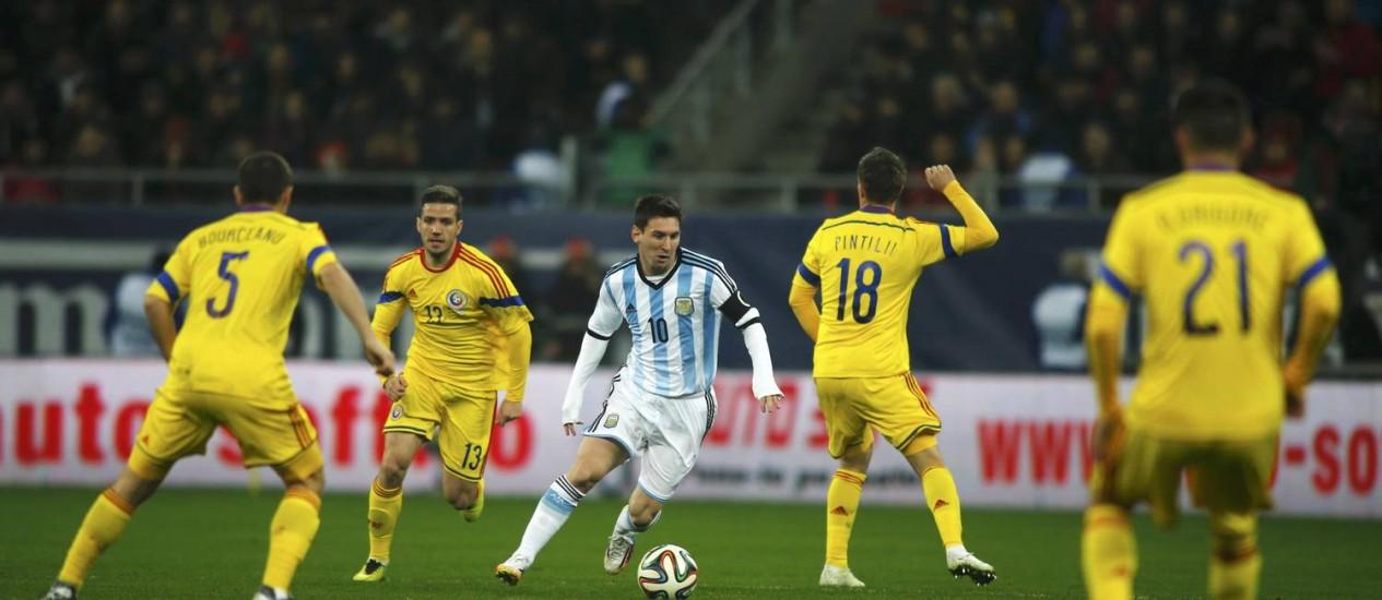 Messi cercado de marcadores em um amistoso entre Argentina e Romênia Foto: BOGDAN CRISTEL / REUTERS