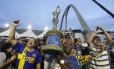 Integrantes da Unidos da Tijuca levam a taça de campeã do carnaval de 2014