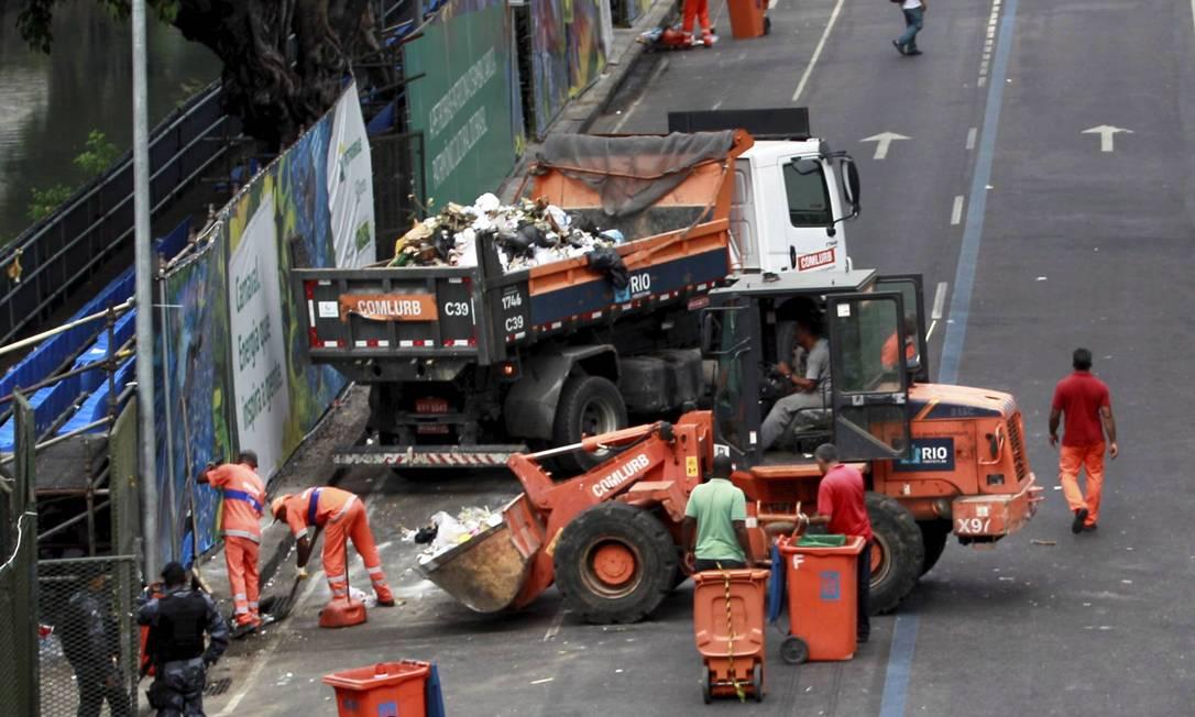 Garis recolhem lixo da Avenida Presidente Vargas escoltados por policiais do Batalhão de Choque Foto: Marcelo Piu / Agência O Globo