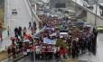 Debaixo de chuva, garis grevistas caminham pela Avenida Presidente Vargas