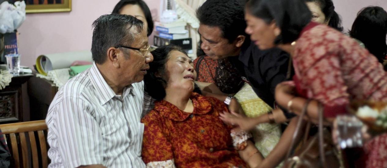 Familiares confortam Chrisman Siregar (à esq.) e sua mulher, Herlina Panjaitan, pais de Firman Siregar, um dos cidadãos da Indonésia que está na lista dos passageiros a bordo do avião desaparecido da Malaysia Airlines Foto: Binsar Bakkara / AP