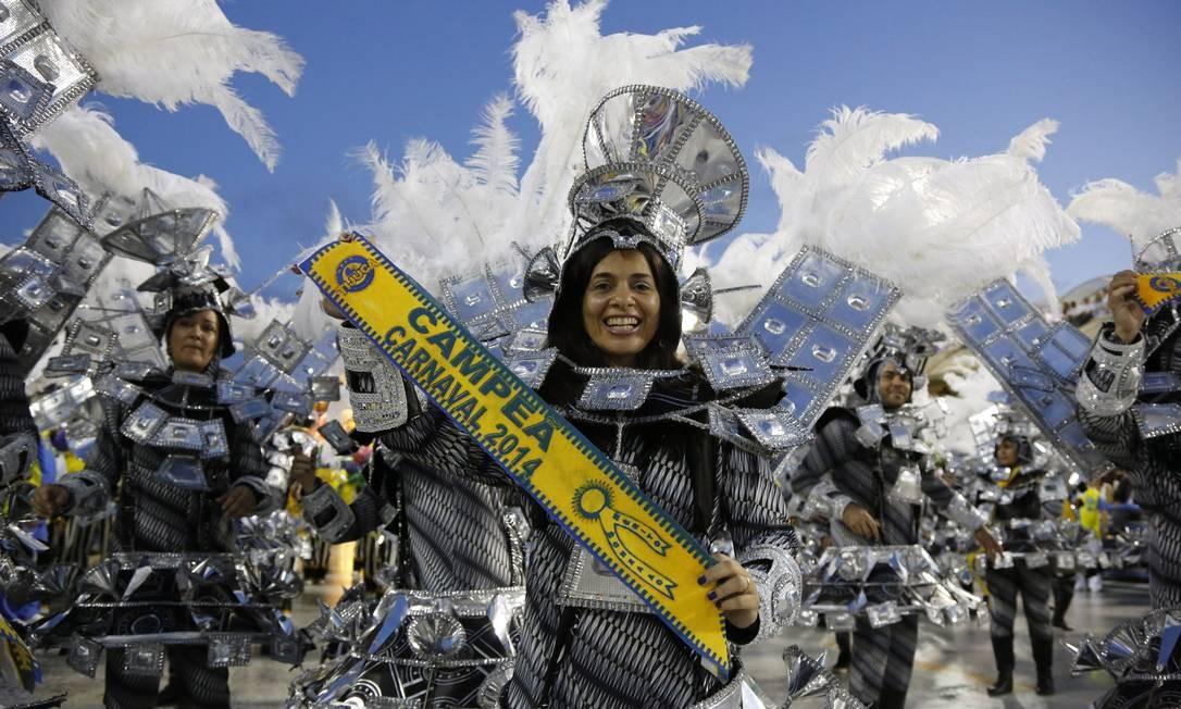 Integrante da Unidos da Tijuca leva a faixa de campeã do carnaval para o desfile Foto: Fabio Rossi / O Globo