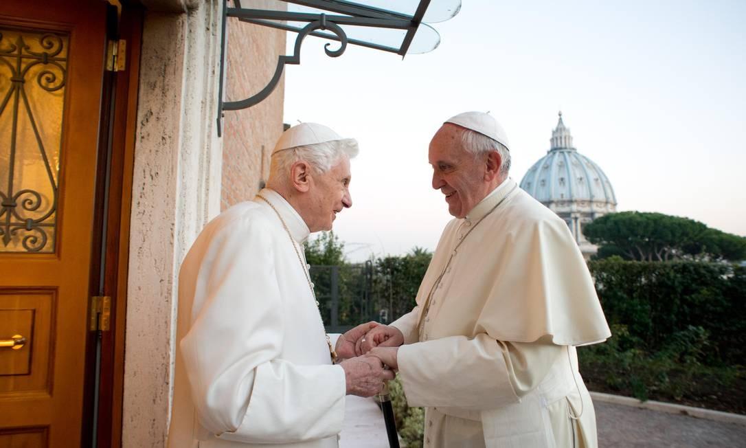 Imagem rara: o Papa Emérito Bento XVI segura as mãos de Francisco em encontro no dia 23 de dezembro de 2013 Foto: AFP-23-12-2014