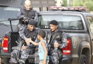 Menino cumprimenta policiais durante a ocupação Foto: Pablo Jacob / Agência O Globo