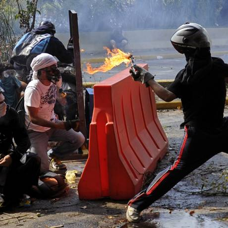 Manifestante atira um coquetel molotov em Caracas, na última quarta-feira Foto: LEO RAMIREZ / AFP