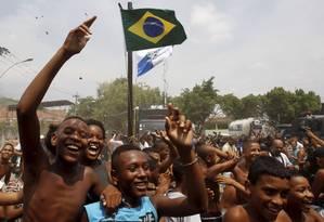 Moradores comemoram a ocupação após policiais hastearem as bandeiras do Brasil e do Estado do Rio na Vila Kennedy - Foto: Pablo Jacob / Agência O Globo
