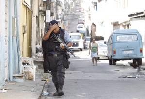 Policial militar patrulha rua do Parque Proletário, após ataque de traficantes que matou o subcomandante da UPP da comunidade na noite desta quinta-feira. A PM reforçou o policiamento no local Foto: Márcia Foletto / O Globo