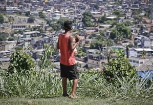 Menino solta pipa no alto do Complexo do Alemão neste domingo - Foto: Guito Moreto / Agência O Globo