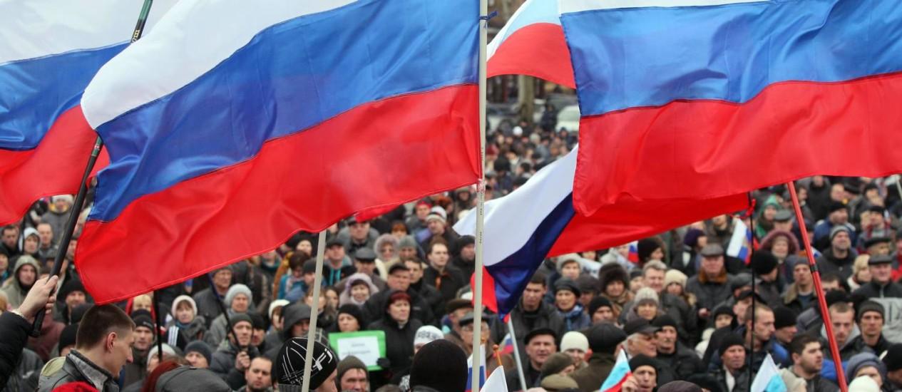 Cidadãos crimeios pró-Rússia agitam bandeiras do país em dia de referendo, na cidade de Donetsk Foto: Alexander KHUDOTEPLY / AFP
