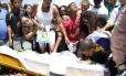 Marido (de blusa azul e amarela), filhos e demais parentes se despedem de Cláudia, que teve o corpo arrastado depois de ser colocada dentro do porta-malas de um carro da PM