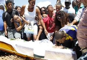 Marido (de blusa azul e amarela), filhos e demais parentes se despedem de Cláudia, que teve o corpo arrastado depois de ser colocada dentro do porta-malas de um carro da PM Foto: Márcia Foletto / Agência O Globo