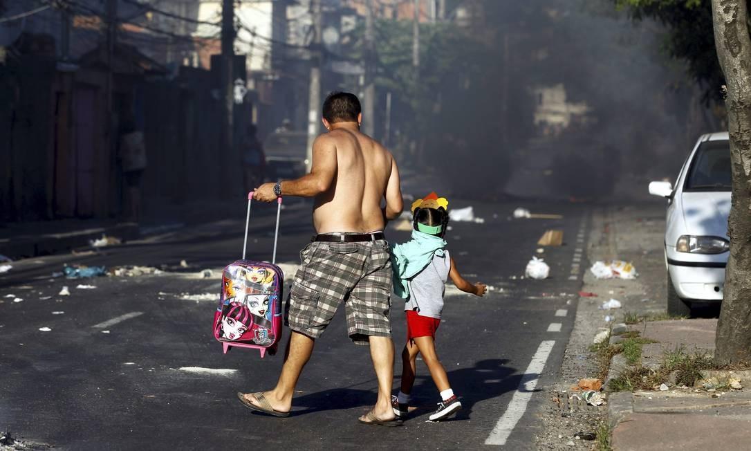 Homem atravessa a rua com criança: ele usou a própria camisa para protegê-la da fumaça Foto: Marcelo Carnaval / Agência O Globo
