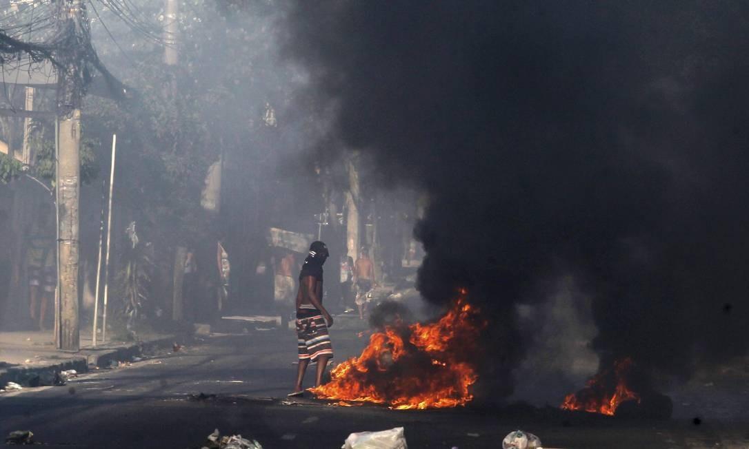 Homem fica parado em frente à barricada em chamas, na Rua Leopoldino de Oliveira, perto do Morro do Cajueiro Foto: Marcelo Carnaval / Agência O Globo