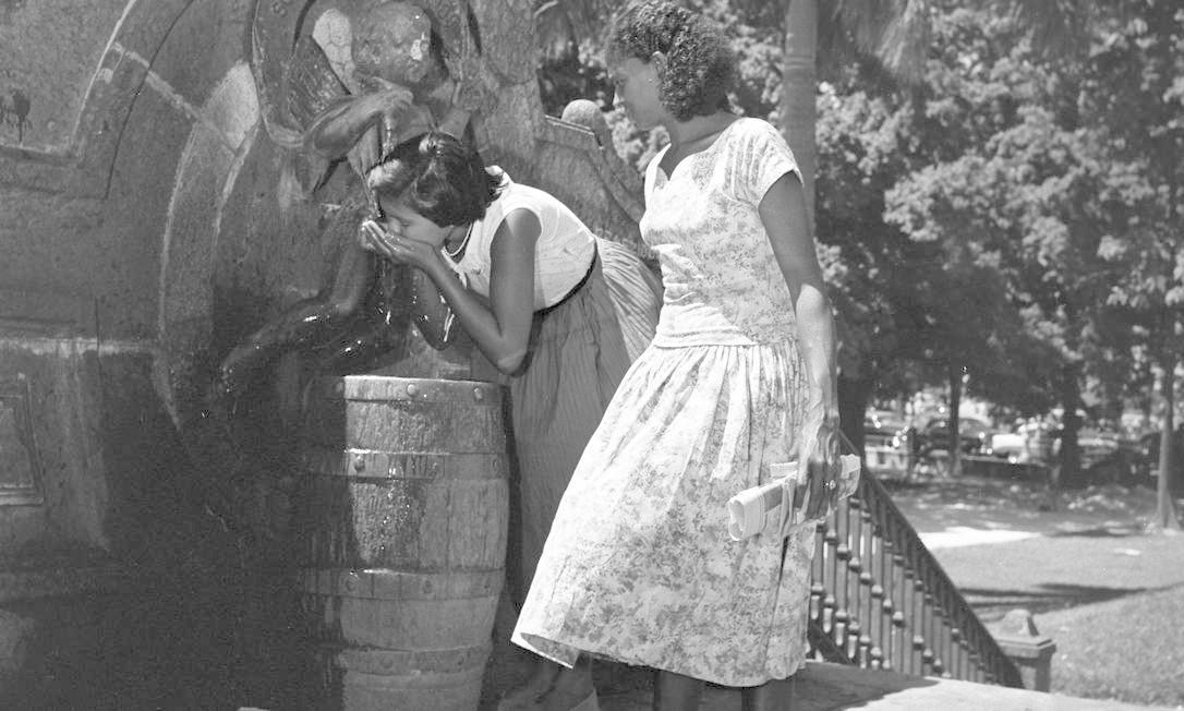 No verão de 1958, duas moças se refrescam do calor bebendo água no chafariz Arquivo / Agência O Globo
