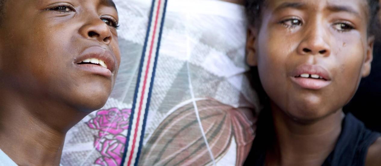 Os filhos gêmeos de Cláudia, Pablo e Pâmela, choram durante o velório. Parentes e amigos pediram justiça quando o caixão desceu Foto: Márcia Foletto / Agência O Globo