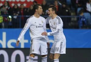 Cristiano Ronaldo, cumprimentado por Bale, é o artilheiro da Liga dos Campeões. E o Real Madrid tem o melhor ataque da competição Foto: Andres Kudacki / AP