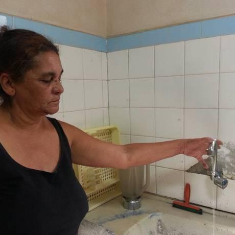 Edna Ribeiro abre a toneira da cozinha e apenas um fio de água cai Foto: O Globo / Jaqueline Falcão