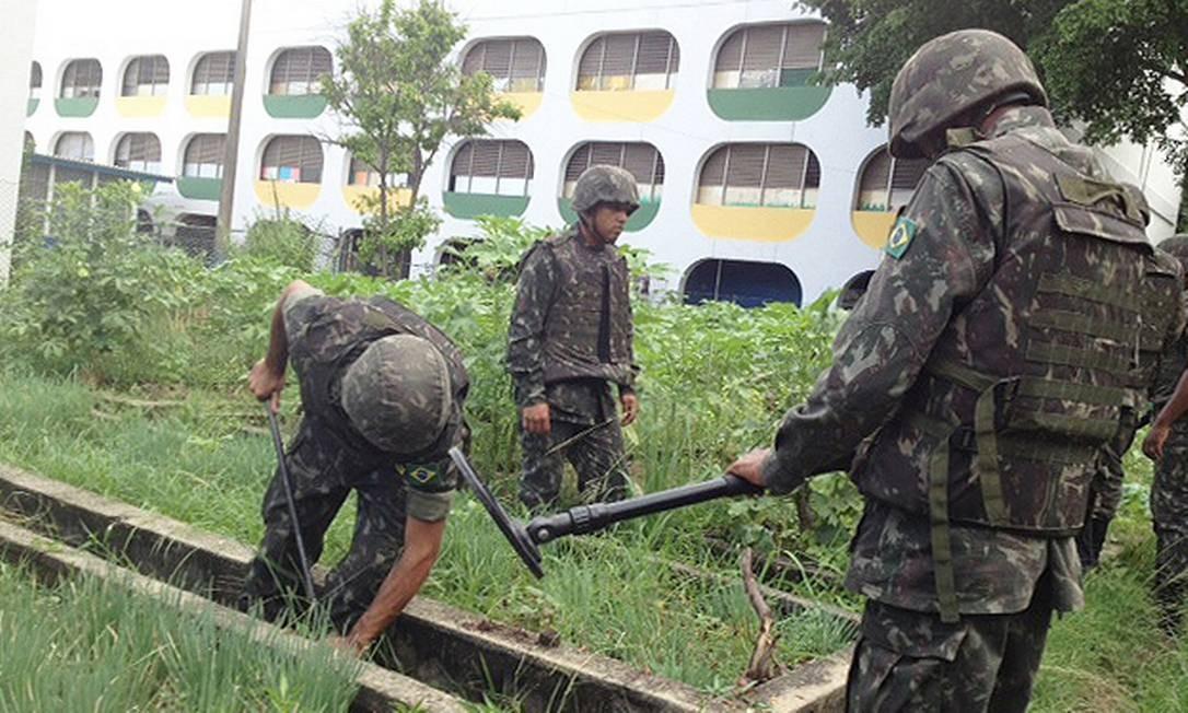 Soldados do Exército procuram armas na horta num Ciep, no Complexo da Maré Foto: Marcia Foletto / Agência O Globo