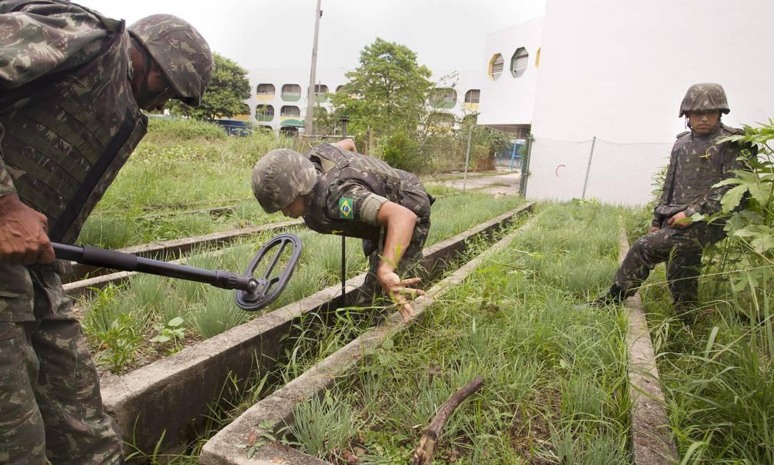 Homens do exército procuram armas na horta do Ciep Samora Machel Foto: Márcia Foletto / Agência O Globo
