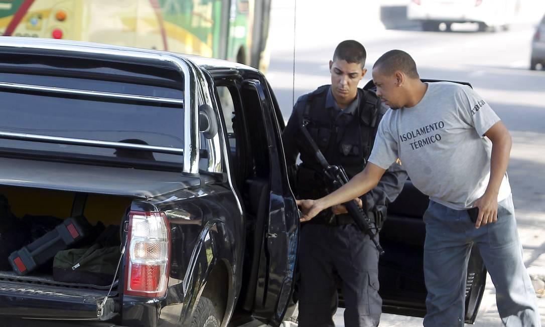 Policiais militares revistam carros de moradores que saem da Vila do João, no Complexo da Maré, neste sábado, um dia antes da ocupação Foto: Gabriel de Paiva / Agência O Globo