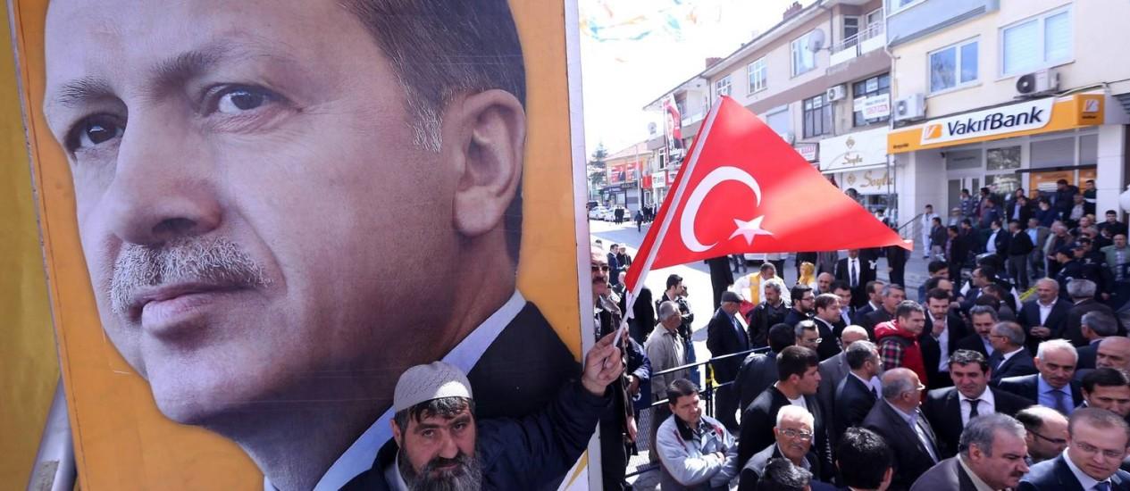 Apoio. Um homem agita a bandeira turca diante de pôster de Erdogan Foto: ADEM ALTAN / AFP