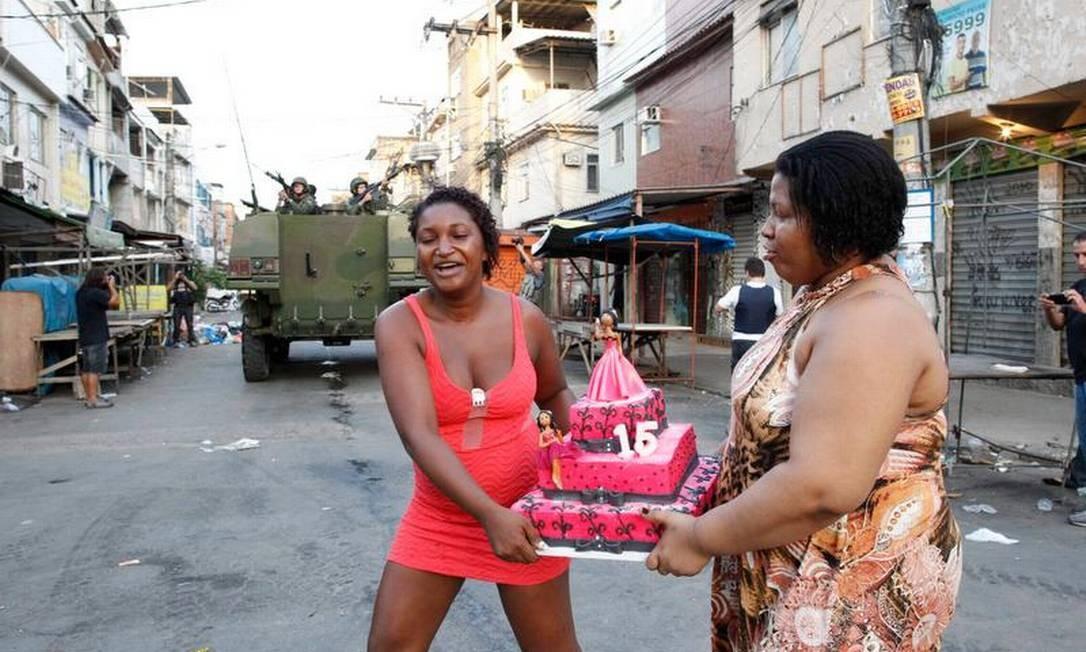 Moradoras da Maré carregam bolo de aniversário: festa no dia da ocupação do complexo Foto: Pablo Jacob