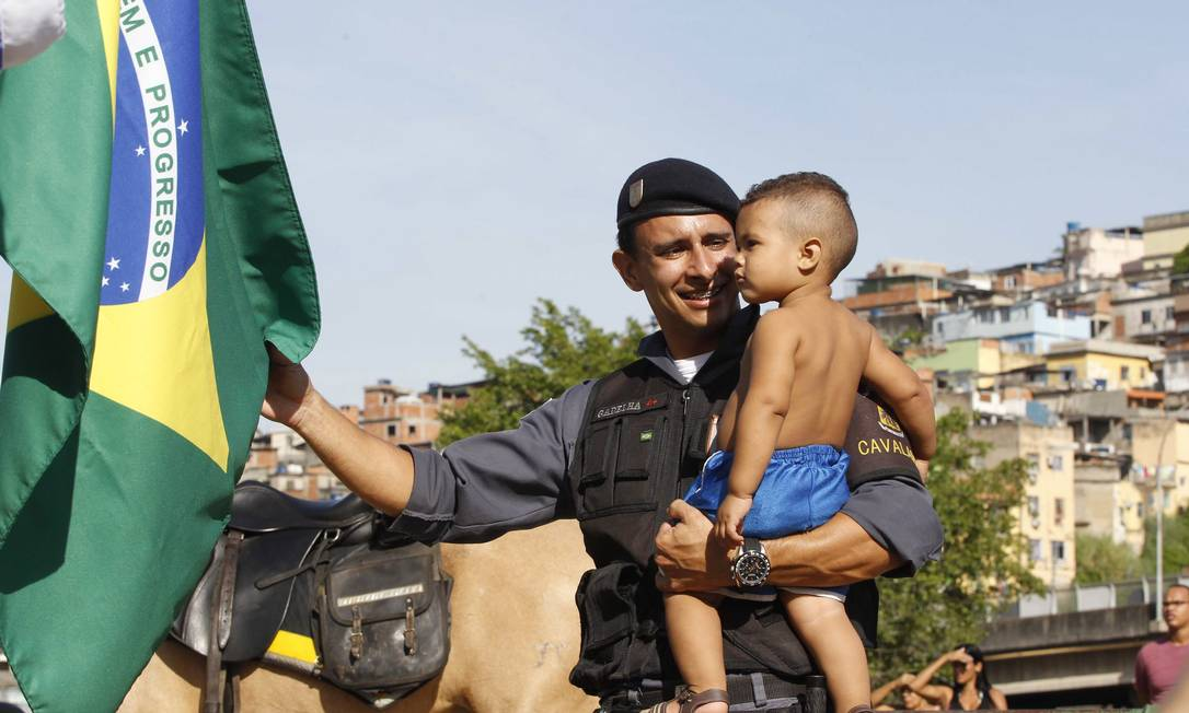 Policial mostra a bandeira do Brasil para o pequeno morador do Complexo da Maré Foto: Pablo Jacob / Agência O Globo
