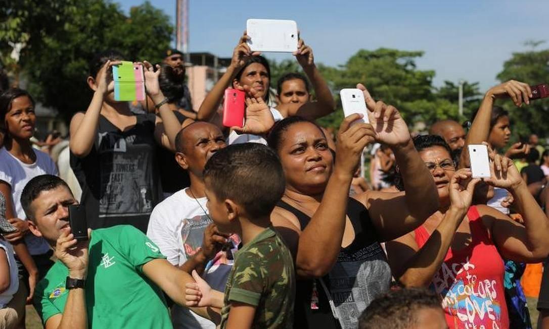Moradores da Maré registram a ocupação com seus celulares e tablets Foto: Leo Correa / AP