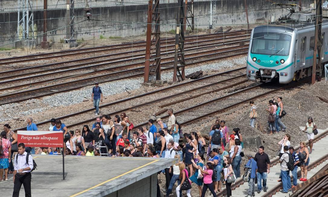 Após trem apresentar problema, passageiros são obrigados a andar pelos trilhas da SuperVia Foto: Alexandre Cassiano / Agência O Globo