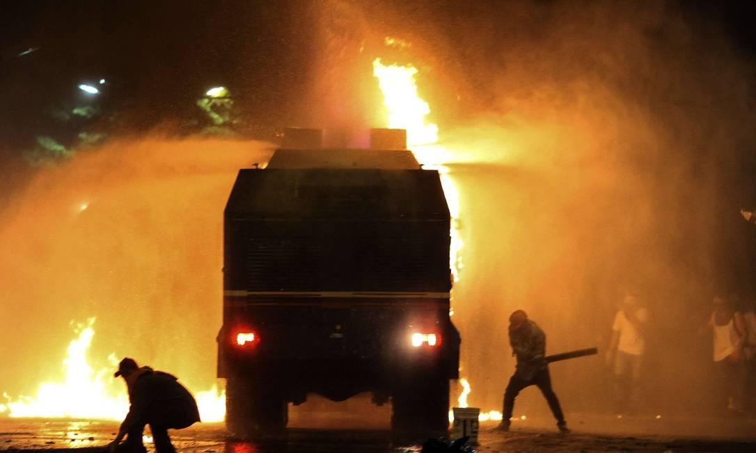 Manifestantes entram em confronto com policiais em Caracas, na noite de domingo Foto: FEDERICO PARRA / AFP