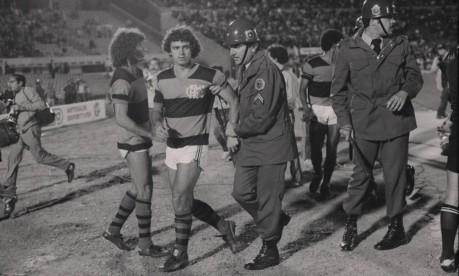 Briga em campo. Em Montevidéu, Anselmo (ao lado de Nunes) deixa o gramado escoltado pela polícia na final da Libertadores, em 1981, em que o Flamengo venceu o Cobreloa por 2 a 0 Foto: Anibal Philot / O Globo