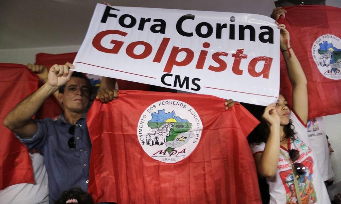 """Manifestantes seguram bandeira que diz """"Fora Corina, golpista"""" durante o discurso do líder da oposição venezuelana Foto: UESLEI MARCELINO / REUTERS"""