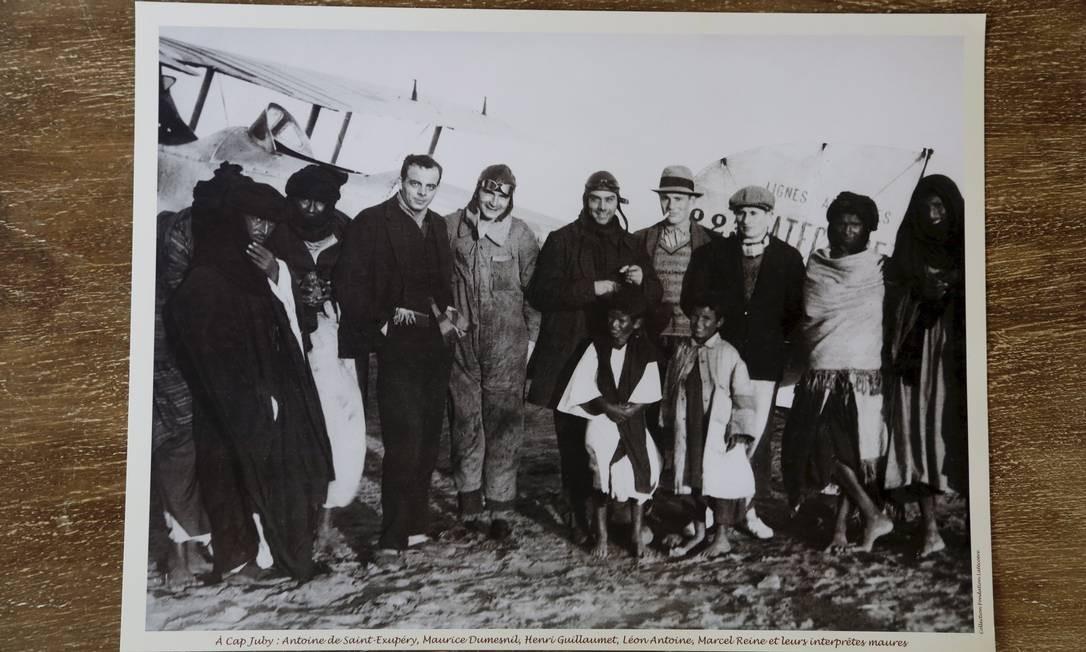 Em Cabo Juby, no Marrocos, os amigos pilotos Antoine de Saint-Exupéry (sem chapéu), Henry Guillaumet (ao centro, todo de preto) e Marcel Reine (de boina) posam ao lado de dois outros aviadores da companhia francesa e de alguns mouros da região. Foto: Hudson Pontes / Agência O Globo