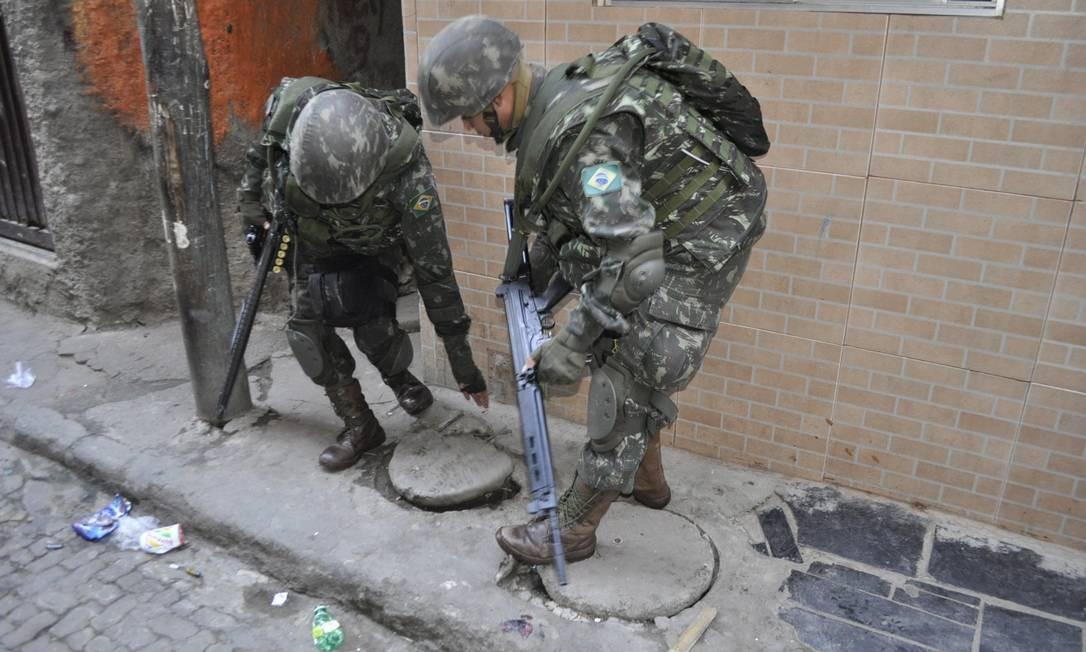 Soldados examinam bueiros em busca de drogas Foto: Gabriel de Sordi / Agência O