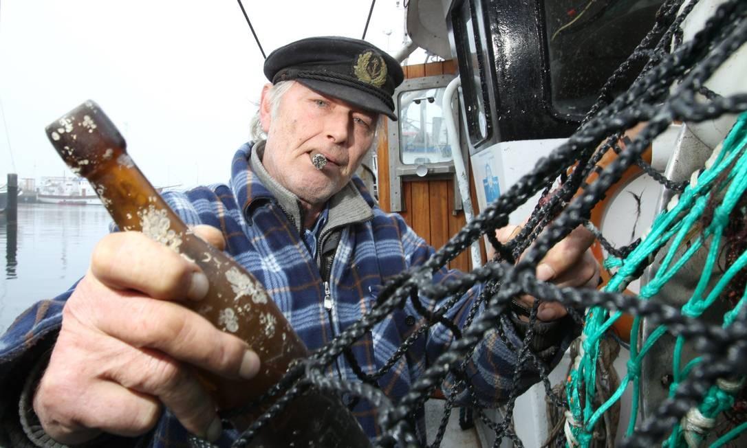 Descoberta. Pescador alemão Konrad Fischer descobriu a mensagem na garrafa em março, nas águas do Mar Báltico. O documento, que passou 101 anos no mar, é a mensagem na garrafa mais antiga já encontrada, segundo o Museu Marítimo de Hamburgo Foto: UWE PAESLER / AFP